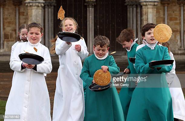 Probationers from Salisbury Cathedral Choir flip pancakes in front of Salisbury Cathedral on February 5 2013 in Salisbury England The trainee...