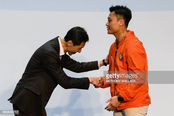 ProBeijing candidate Vincent Cheng is congratulated by disqualified prodemocracy lawmaker candidate Edward Yiu after Cheng won the seat for the...