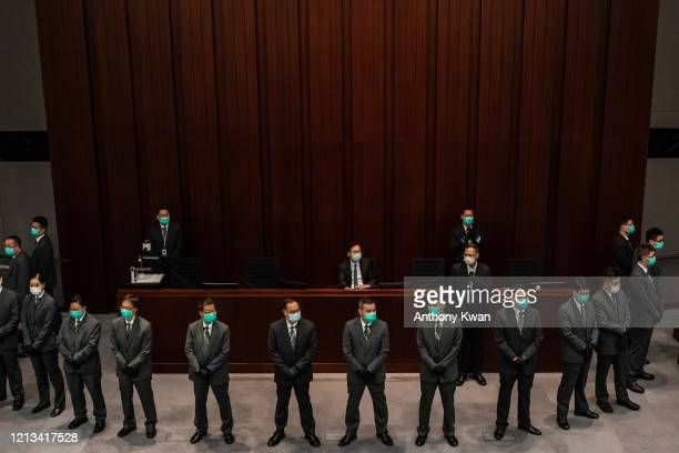ProBeijing lawmaker Chan Kin Por is surrounded by security officers ahead of a meeting at the Legislative Council in May 18 2020 in Hong Kong China...