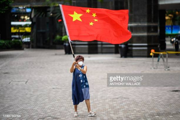 Pro-Beijing supporter waves a Chinese flag in Hong Kong on June 30 on the eve of the 100th anniversary of the Chinese Communist Party and the 24th...