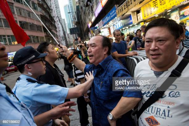 A proBeijing supporter waving Chinese flags is held back by police as he tries to argue with prodemocracy activists gathering for a candlelight vigil...