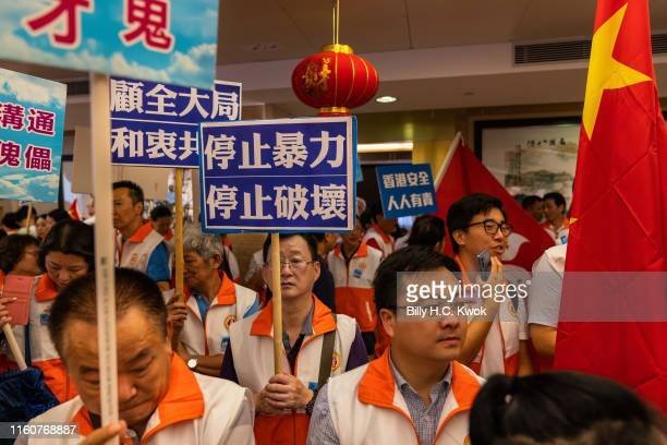 ProBeijing supporters hold placards and shout slogans as they gather at the Hong Kong Federation of Fujian Associations to show support for the Hong...