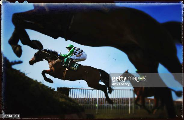 Problema Tic ridden by Tom Scudamore jumps a fence during The John Smith's Handicap Steeple Chase at Aintree Racecourse on April 6 2013 in Liverpool...