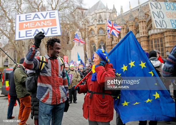 Pro-Brexit activist holding a placard and wearing a union flag-themed shirt talks with an anti-Brexit demonstrator holding an EU flagas they protest...