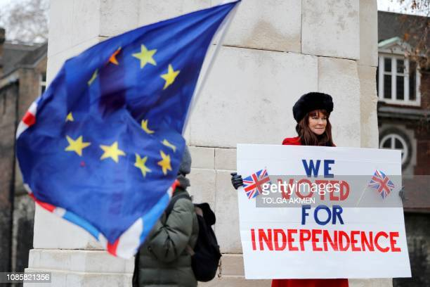 A proBrexit activist holds a placard reading We Voted For Independence as an antibrexit campaigner waves an Eropean Union and a Union flag as they...