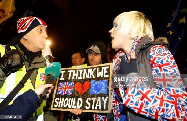 Pro-Brexit activist wearing a 'yellow vest' hi-vis jacket remonstrates with an anti-Brexit activist dressed in an Union flag-themed jacket, as they...