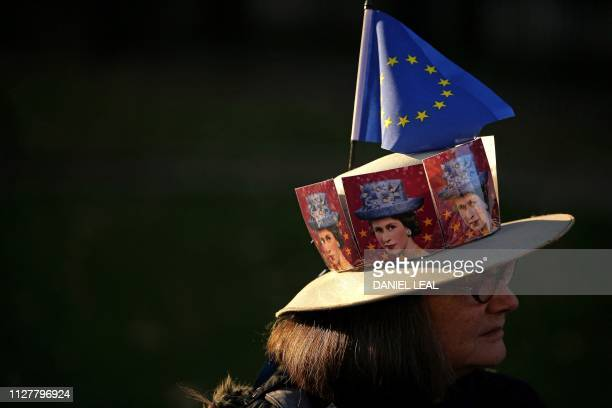 TOPSHOT A proBrexit activist wears a hat decorated with pictures of Britain's Queen Elizabeth II and an EU flag as they demonstrate outside the...