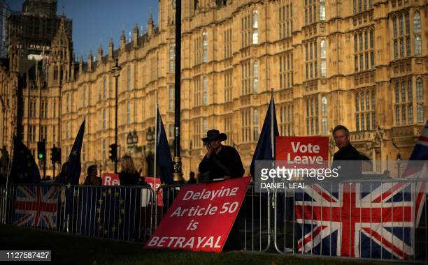 TOPSHOT ProBrexit activists hold placards as they demonstrate outside of the Houses of Parliament in London On February 26 2019 British Prime...