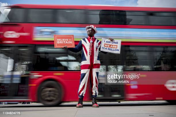 A proBrexit campaigner wears the Union flag colours and holds placards as he demonstrates near the Houses of Parliament in central London on April 3...