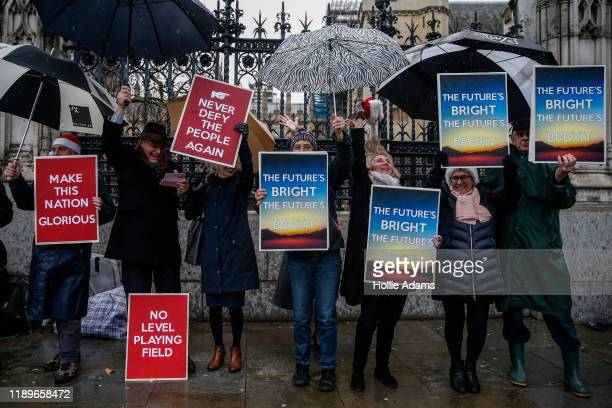 ProBrexit campaigners celebrate while hold placards near the Houses of Parliament on December 20 2019 in London England The EU Withdrawal Agreement...