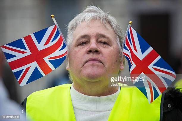 A proBrexit demonstrator with Union Jack flags in their ears protests outside the Houses of Parliament on November 23 2016 in London England British...