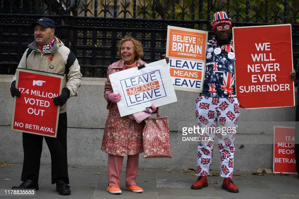Pro-Brexit demonstrators hold placards as they stand outside the Houses of Parliament in central London on October 29, 2019. - Britain was on course...