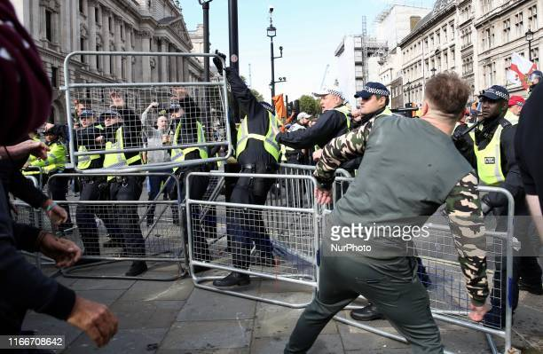 ProBrexit demonstrators throw a metal barrier at policemen during clashed with polce forces at Parlament Square London England on Saturday September...