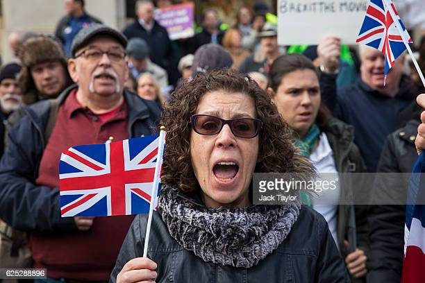 ProBrexit demonstrators wave Union Jack flags as they protest outside the Houses of Parliament on November 23 2016 in London England British Prime...