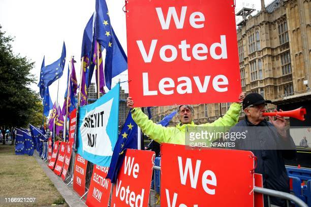 """Pro-Brexit protester holds up a """"We Voted Leave"""" placard outside the Houses of Parliament in London on September 9, 2019. - British Prime Minister..."""
