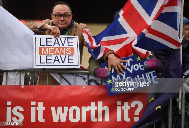 A proBrexit protester pushes away the placard of a supporter of a second EU referendum outside the Houses of Parliament in central London on January...
