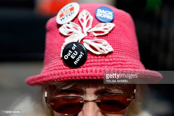 Pro-Brexit protester wears a hat with anti-EU messages on badges outside the Houses of Parliament in central London on September 3, 2019. - The fate...