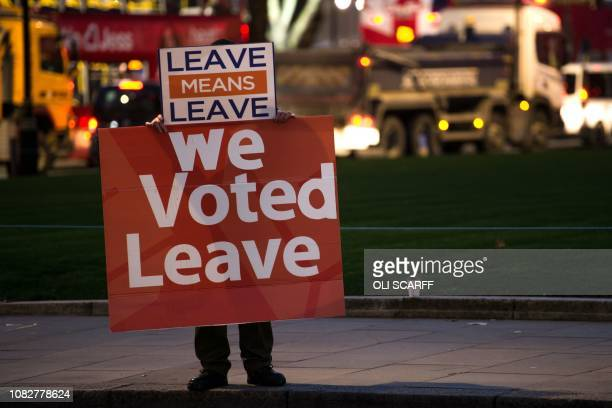 TOPSHOT A proBrexit supporter holds up a placard as he demonstrates outside the Houses of Parliament in central London on January 14 2019 Prime...