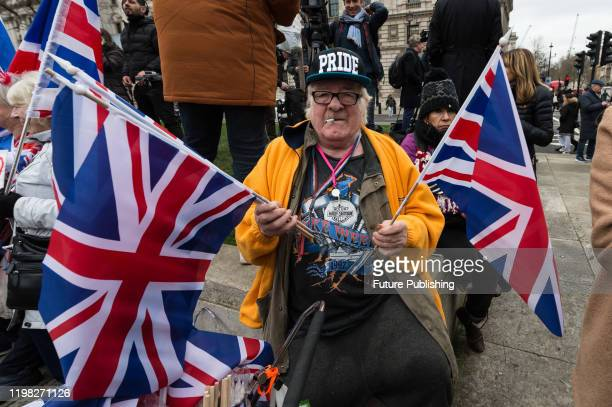 Pro-Brexit supporter waves British flags in Parliament Square as he celebrates Brexit day on 31 January, 2020 in London, England. Today, Britain...