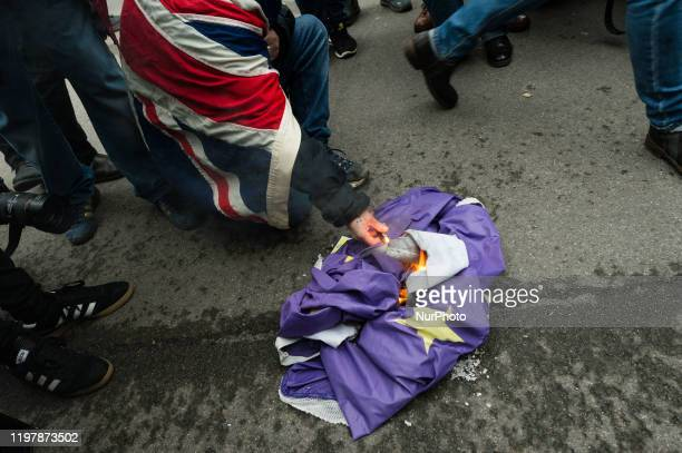 ProBrexit supporter wrapped in a Union Jack flag burns a flag of the EU outside Downing Street as thousands celebrate Brexit day on 31 January 2020...