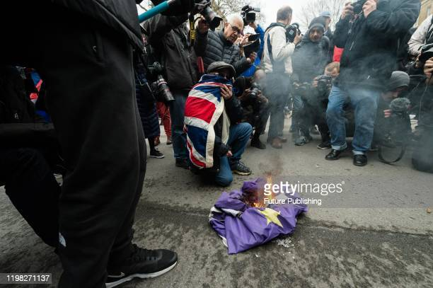 Pro-Brexit supporter wrapped in a Union Jack flag is surrounded by photographers as he burns a flag of the EU outside Downing Street as thousands...
