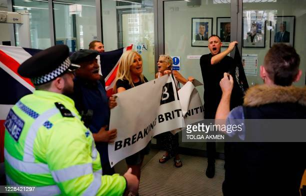 Pro-Brexit supporters display banners as they enter the reception at Europe House, headquarters of the EU Delegation to the UK, in central London on...