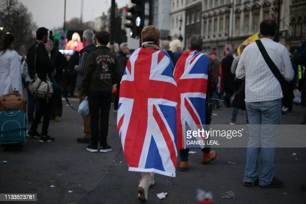 ProBrexit supporters draped in Union Flags leave at the end of a rally outside the Houses of Parliament in central London on March 29 2019 after MPs...