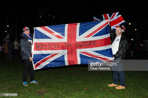 Pro-Brexit supporters hold Union Jack flags as they take part in a rally celebrating Britain's departure from the EU in Parliament Square on 31...