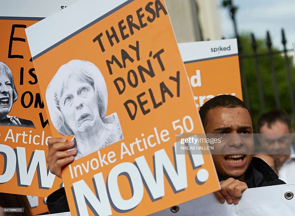 Pro-Brexit supporters holds up placards as they demonstrate outside Downing street in central London on July 13, 2016, on the day new British Prime Minister Theresa May takes over at number 10. Theresa May took office as Britain's second female prime minister on July 13 charged with guiding the UK out of the European Union after a deeply devisive referendum campaign ended with Britain voting to leave and David Cameron resigning. / AFP / NIKLAS HALLE'N