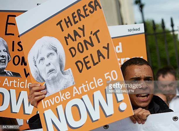 ProBrexit supporters holds up placards as they demonstrate outside Downing street in central London on July 13 on the day new British Prime Minister...