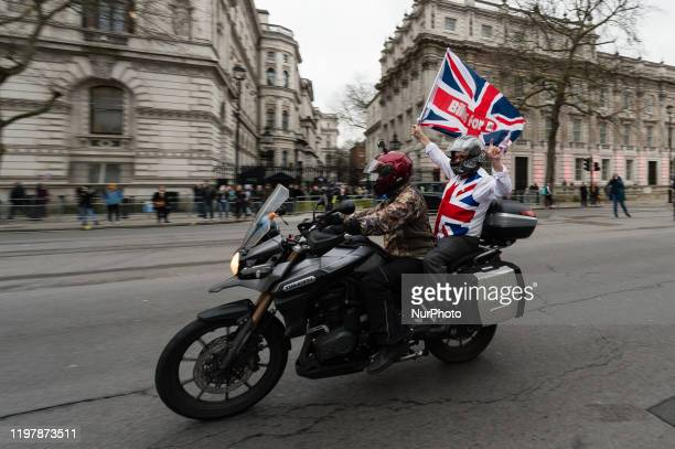 Pro-Brexit supporters ride a motorcycle waving a British flag past Downing Street to mark Brexit day on 31 January, 2020 in London, England. Today,...
