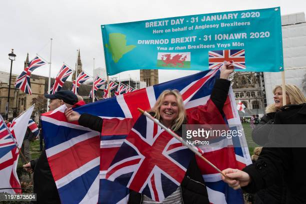 ProBrexit supporters wave British flags in Parliament Square as they celebrate Brexit day on 31 January 2020 in London England Today Britain formally...