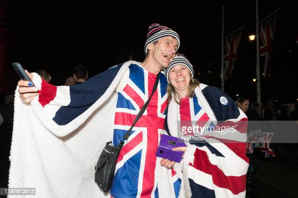 Pro-Brexit supporters wear Union Jack flags as they take part in a rally celebrating Britain's departure from the EU in Parliament Square on 31...
