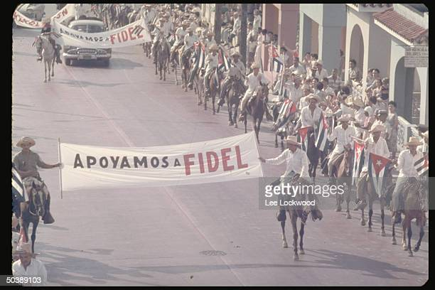 ProCastro rebels on horseback entering city displaying banners saying APOYAMOS A FIDEL on day of huge victory celebration