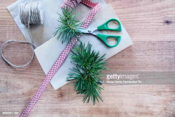 Procces of decorating Christmas gifts on wood background. Overhead and copy space