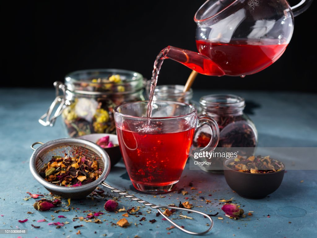 Process brewing tea, tea ceremony, Cup of freshly brewed fruit and herbal tea, dark mood. Hot water is poured from the kettle into a cup with tea leaves. : Stock Photo