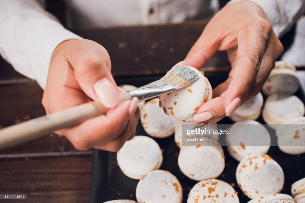 Process making macaroons. Shallow focus. brush with food paint : Stock Photo