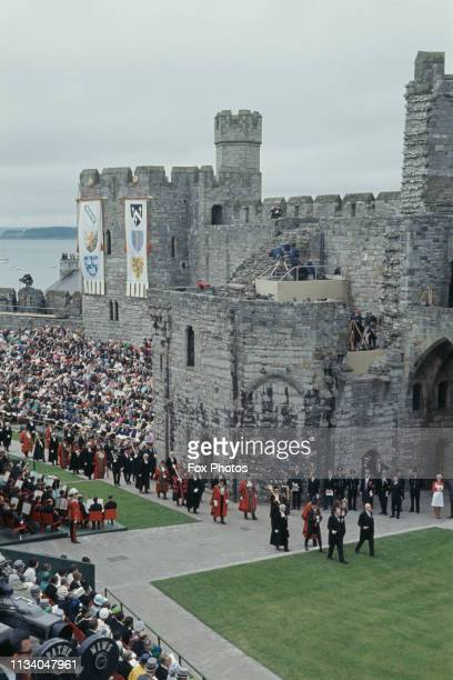A procession at Caernarfon Castle Gwynedd during the investiture of Prince Charles as Prince of Wales 1st July 1969 The castle walls are hung with...