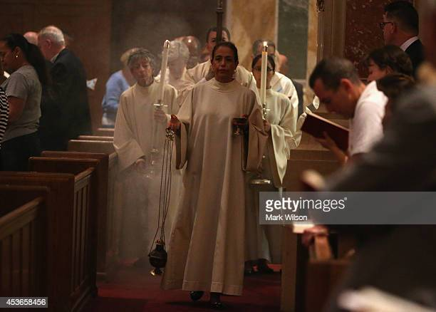 A procession escorts Cardinal Donald Wuerl to the alter to conduct Mass to mark the Assumption of the Blessed Virgin Mary a Holy Day of Obligation...