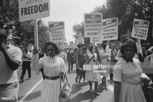 Procession of African Americans carrying signs for equal rights integrated schools decent housing and an end to bias