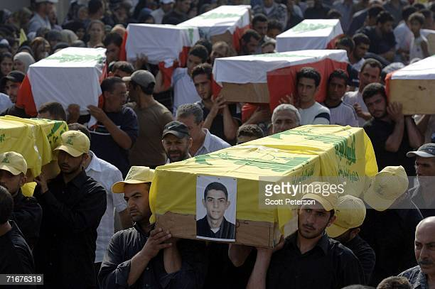 A procession of coffins are carried through the streets as most of the civilian victims of an Israeli air strike are formally buried August 18 2006...
