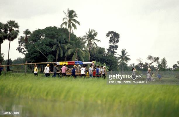A procession of locals passing through the countryside on the outskirts of Yasothon on their shoulders they carry the enormous 3 to 4 metre long...
