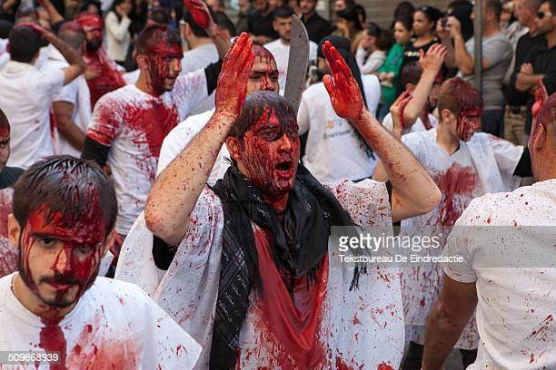 A procession of shi'ite muslim men carrying swords and knives covered in their own blood on the streets of Nabatieh Lebanon on the Day of Ashura...