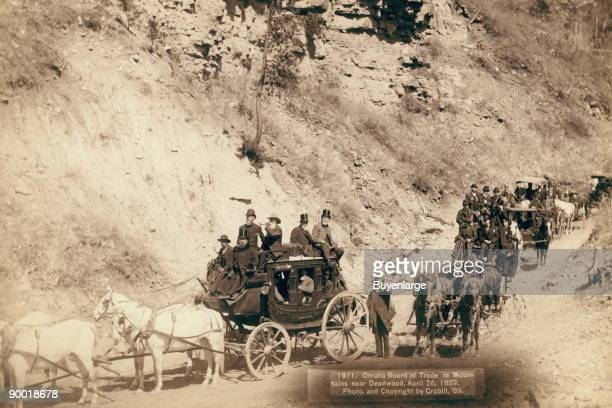 Procession of stagecoaches loaded with passengers coming down a mountain road April 26 1889