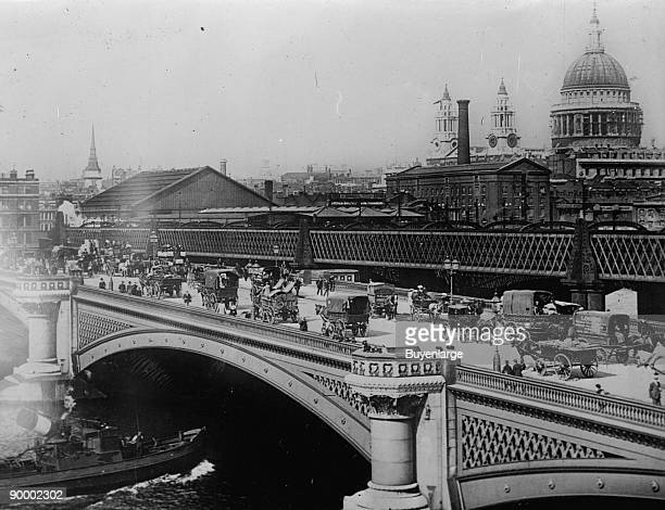 Procession of traffic in Horse Drawn Vehicles crosses London's Black Friar's Bridge in 3/4 elevation with the Thames below and St Paul's in the...