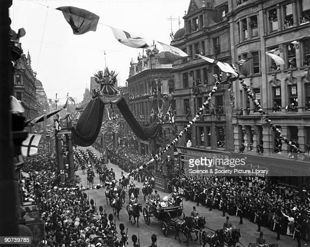 Procession passing along a busy London thoroughfare during the Coronation of Edward VII On the right is a J Lyons tea room