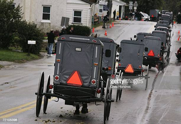 A processional of Amish carriages moves through Georgetown during the funeral of slain Amish schoolgirl Anna Mae Stoltzfus October 6 2006 in Bart...