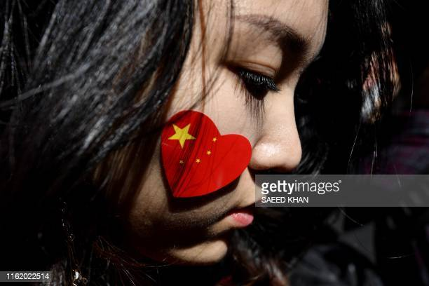 A ProChina activist marches on the streets of Sydney on August 17 as she and others rally against ongoing protests in Hong Kong Hundreds of activists...