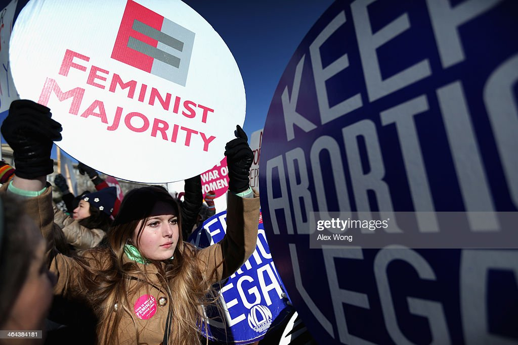 Pro-choice activist and intern of Feminist Majority Foundation Jade Reindl (L) holds a sign as marchers of the annual March for Life arrive in front of the U.S. Supreme Court January 22, 2014 on Capitol Hill in Washington, DC. Pro-life activists from all around the country gathered in Washington for the event to protest the Roe v. Wade Supreme Court decision in 1973 that helped to legalize abortion in the United States.