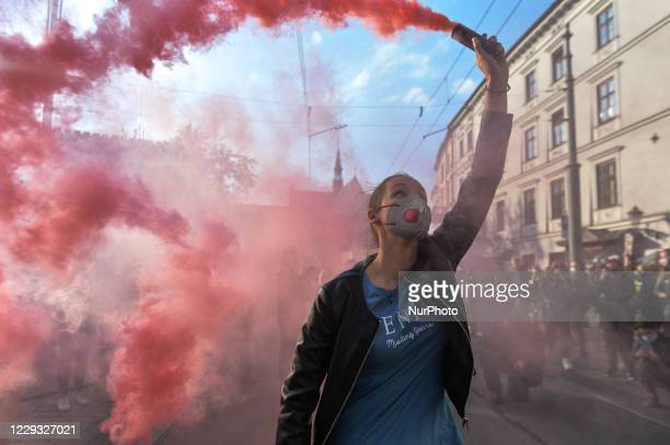 Pro-Choice activist holds a smoke flare during a protest in Krakow's Market Square. Women's rights activists and their supporters staged their...